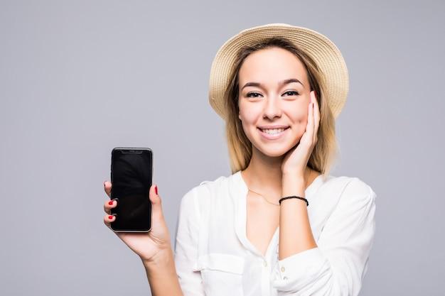 Feche o retrato de uma mulher sorridente, mostrando um celular com tela em branco, em pé, isolado na parede cinza