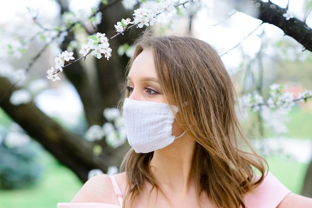 Feche o retrato de uma mulher tenra sob uma árvore em flor com uma máscara