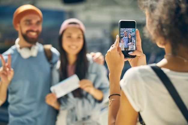 Feche o retrato de uma mulher tirando foto em um celular moderno para dois jovens no aeroporto