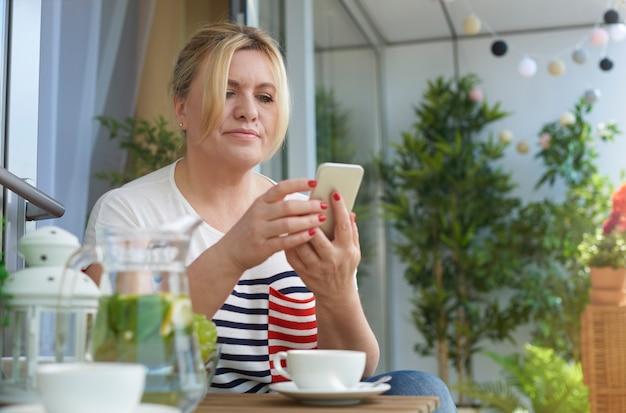 Feche o retrato de uma mulher tomando café na varanda