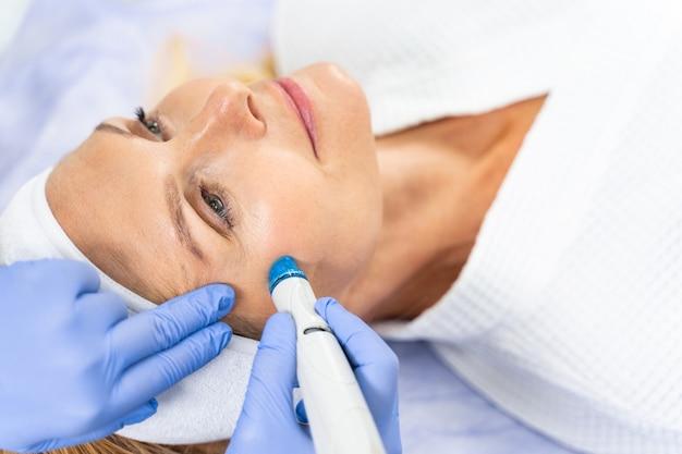 Feche o retrato de uma paciente fazendo um tratamento facial para a pele em uma clínica de beleza