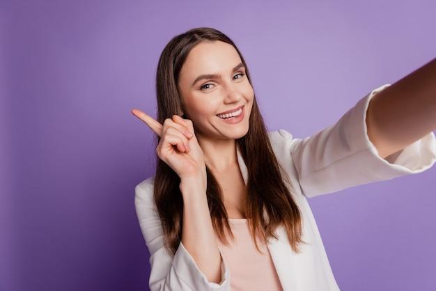 Feche o retrato de uma senhora alegre, segure a câmera e indique o dedo para cima, use um terno formal posando na parede violeta