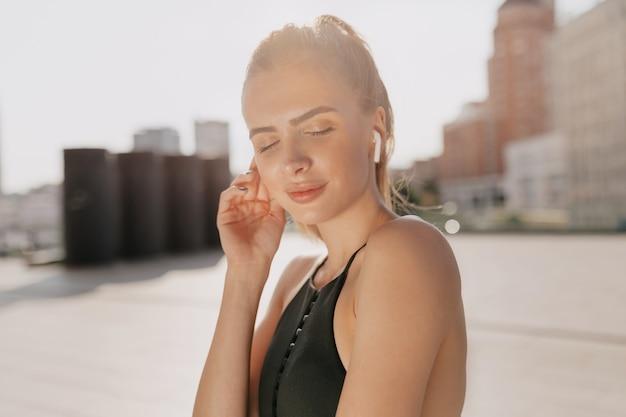 Feche o retrato de uma senhora muito charmosa envolvida em exercícios de esportes e ouvindo música na luz do sol na cidade. esporte, exercício