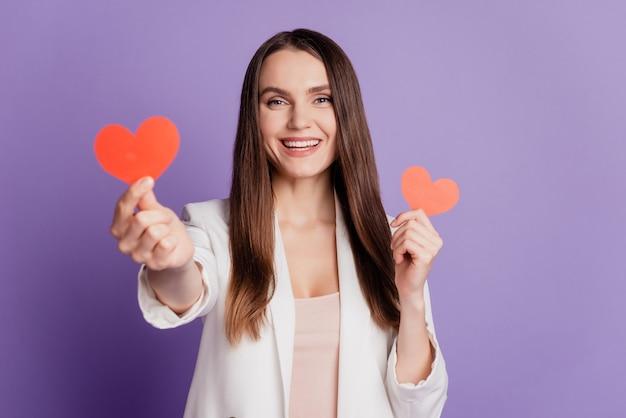 Feche o retrato de uma senhora segurando dois pequenos cartões em forma de coração e vestindo um terno formal posando na parede roxa