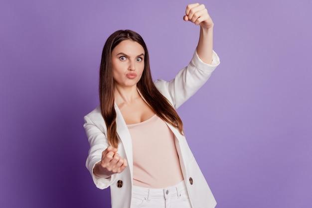Feche o retrato de uma senhora sonhadora com as mãos segurando um volante imaginário e vestindo um terno formal posando na parede violeta