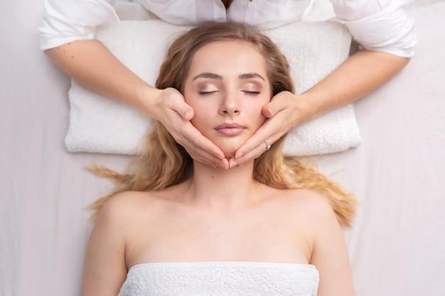 Feche o retrato de uma terapia energética com um curandeiro, segurando a cabeça de uma jovem.