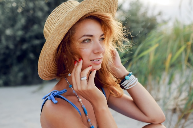 Feche o retrato de verão de alegre linda mulher com chapéu de palha relaxante na praia ensolarada nas férias. clima tropical.