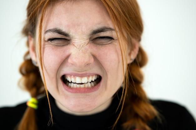 Feche o retrato do adolescente com raiva ruiva.