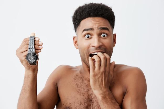 Feche o retrato do atraente americano pele preta sexy com cabelo encaracolado, sem roupas segurando o relógio de mãos dadas, segurando a mão perto da boca, olhando na câmera com expressão assustada.