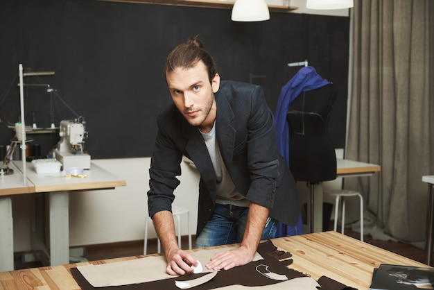 Feche o retrato do atraente designer de moda masculina caucasiano morena atraente, olhando na câmera com expressão relaxada, trabalhando no vestido novo para a coleção de roupas de inverno.