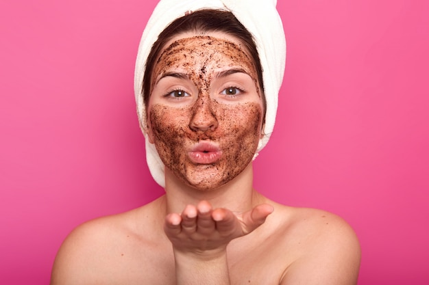 Feche o retrato do belo europeu feminino mandando beijo, colocando a máscara de chocolate, estar nu, penteando o cabelo com uma toalha branca, parece calmo e relaxado. conceito de beleza e cuidados.