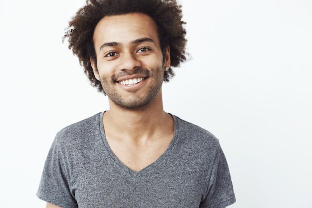 Feche o retrato do cara africano sorrindo, um estudante confiante em sua futura carreira ou um sonho de caçador de cabeça em pé sobre uma parede branca.
