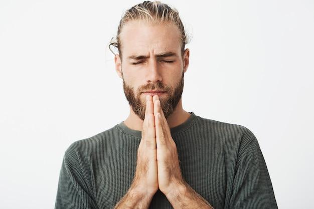 Feche o retrato do cara maduro concentrado com corte de cabelo à moda e barba juntos de mãos dadas na frente, orando e esperando