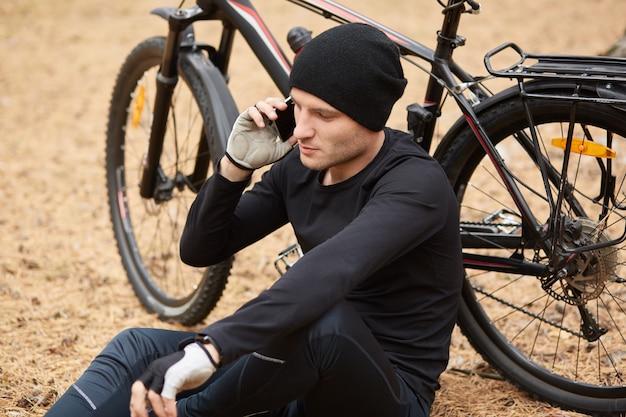 Feche o retrato do ciclista descansando ao ar livre, sentado no chão no campo ou floresta e falando no telefone, usa roupas esportivas e boné