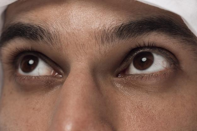 Feche o retrato do empresário da arábia saudita. rosto do jovem modelo masculino, tiro de olhos olhe para cima. conceito de negócios, finanças, expressão facial, emoções humanas.