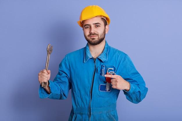 Feche o retrato do engenheiro barbudo com chaves, olhando para a câmera e apontando para sua ferramenta com o dedo indicador, reparador posando contra azul, mecânico veste uniforme e capacete amarelo.