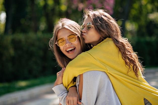 Feche o retrato do estilo de vida de dois amigos adolescentes inspirados felizes, abraços e sorrisos. melhores amigas se divertindo e andando no parque ensolarado de verão. vestindo roupa casual.