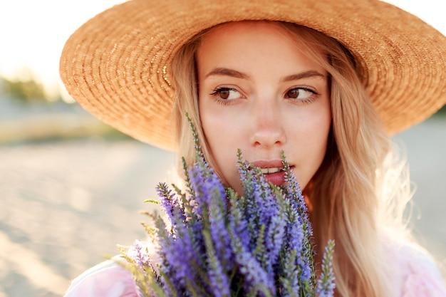 Feche o retrato do estilo de vida de uma mulher loira romântica com flores na mão, caminhando na praia ensolarada. cores quentes do sol.