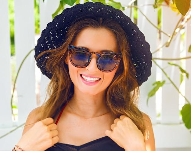Feche o retrato do estilo de vida ensolarado de uma mulher muito sorridente se passando perto de uma parede branca, vindo da praia, usando um elegante chapéu preto e elegantes óculos de sol vintage.