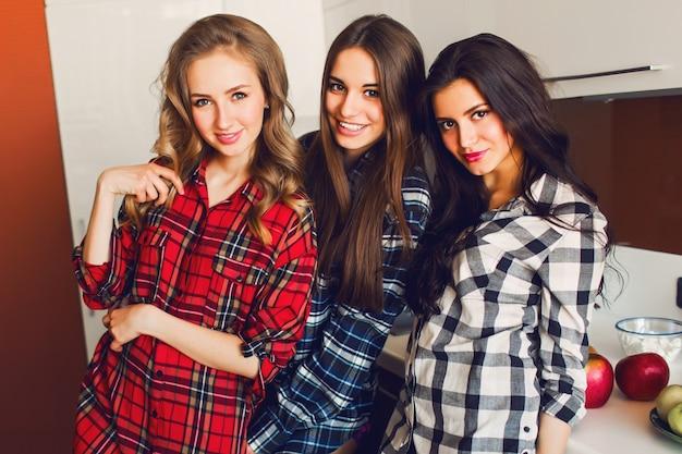 Feche o retrato do estilo de vida interior de três engraçados jovens amigos divirta-se e rostos fingidos na cozinha. humor de festa em casa. vestindo camisa xadrez. foto quente e suave.