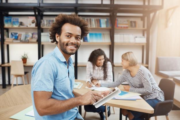 Feche o retrato do estudante universitário bonito sentado na reunião com os amigos após o estudo