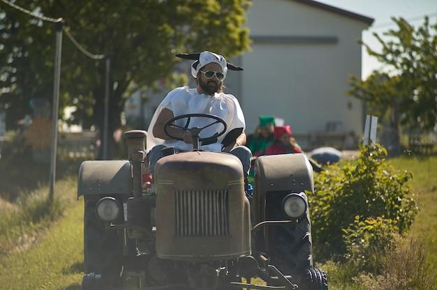 Feche o retrato do fazendeiro engraçado no trator