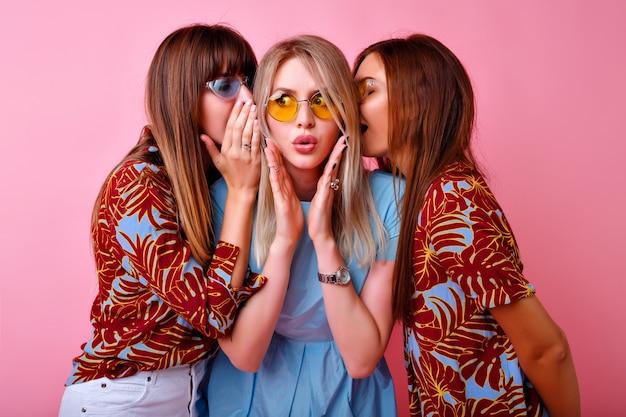 Feche o retrato do grupo engraçado elegante mulher sussurrando segredos uns com os outros, surpreso saiu emoções, cores da moda combinando roupas e óculos. amigos felizes se divertindo
