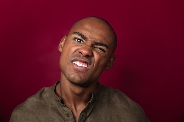 Feche o retrato do homem africano sério mostrando careta e olhando