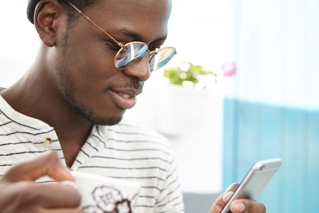 Feche o retrato do homem afro-americano elegante e moderno com roupas da moda, desfrutando de conexão de internet sem fio gratuita no café, tomando café e lendo mensagens on-line enquanto passa férias no exterior
