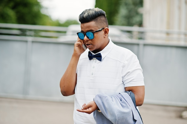 Feche o retrato do homem árabe elegante em óculos de sol e gravata borboleta posou ao ar livre e falando no celular. homem modelo árabe.