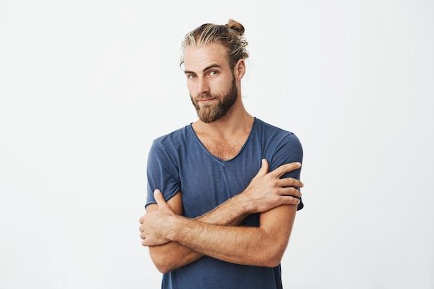 Feche o retrato do homem barbudo atraente com penteado bonito, cruzando as mãos