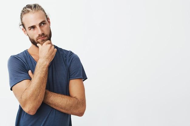 Feche o retrato do homem barbudo bonito com penteado elegante e roupas olhando de lado e pensando