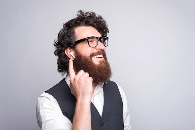 Feche o retrato do homem barbudo de terno sorrindo e usando fones de ouvido.