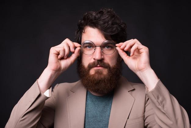Feche o retrato do homem barbudo hipster tocando os óculos