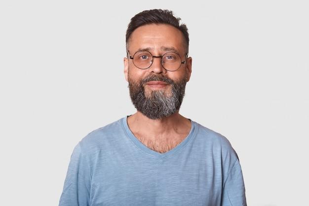 Feche o retrato do homem caucasiano barbudo envelhecido médio bonito com sorriso, homem vestindo camiseta casual cinza, parece satisfeito.