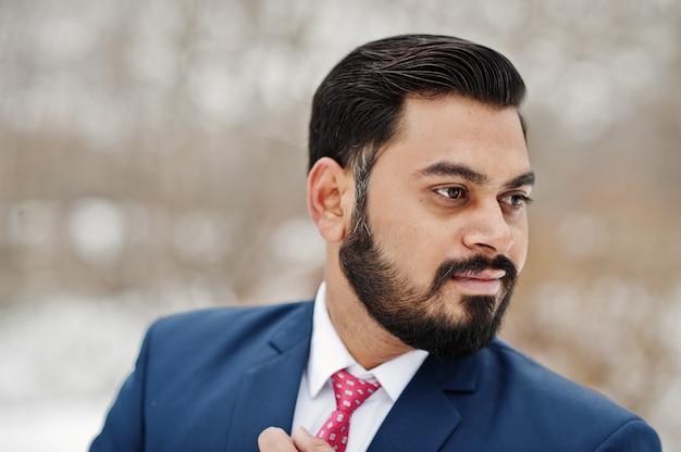 Feche o retrato do homem de negócios de barba indiano elegante terno posando no dia de inverno ao ar livre.