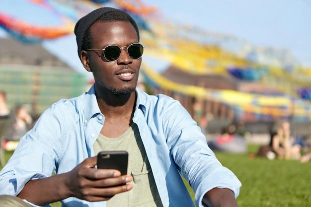 Feche o retrato do homem de pele escura elegante de óculos da moda e camisa, segurando o celular na mão, olhando para a distância enquanto relaxa na grama verde ao ar livre. pessoas, estilo de vida, tecnologia