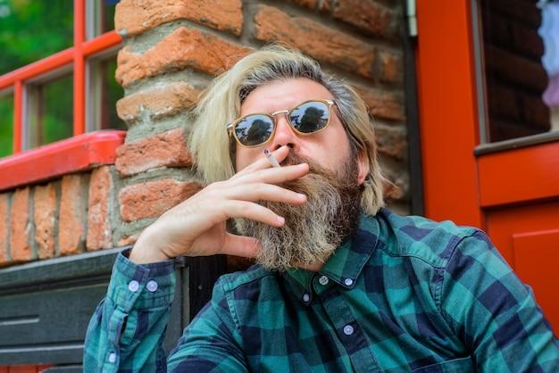 Feche o retrato do homem fumador sensual barbudo hippie com fumaça de cigarro homem barbudo