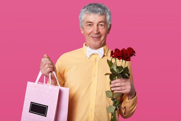 Feche o retrato do homem idoso de cabelos brancos na camisa amarela e gravata branca