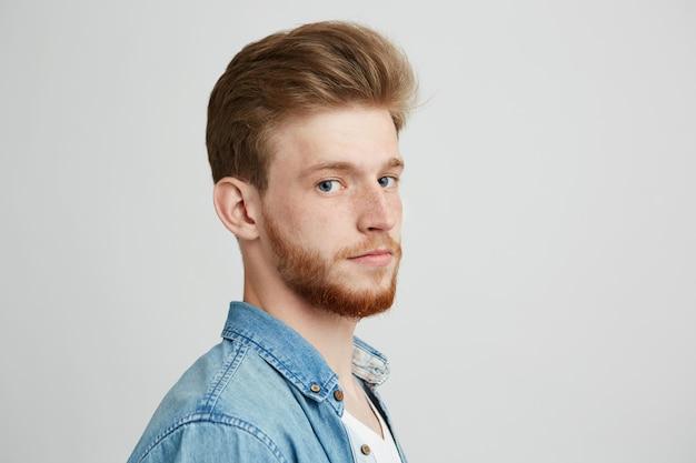 Feche o retrato do homem jovem bonito hipster com barba, vestindo camisa jeans.