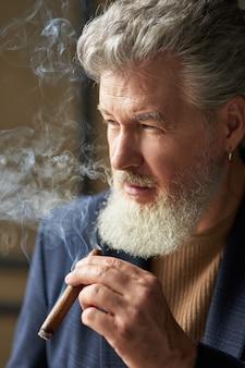 Feche o retrato do homem maduro de cabelos grisalhos sério, olhando para longe enquanto fumava charuto. estilo de vida, sucesso, conceito de pessoas