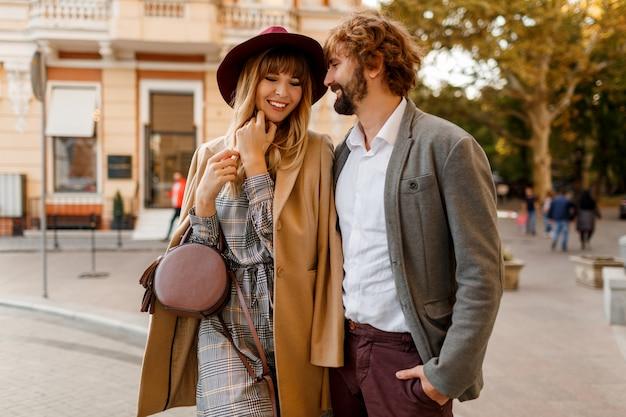 Feche o retrato do incrível casal elegante apaixonado, passando férias românticas na cidade europeia. mulher loira e bonita com chapéu e vestido casual, sorrindo e olhando para seu homem bonito com barba.