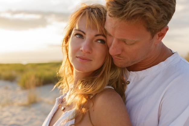 Feche o retrato do incrível lindo casal abraçando contra o pôr do sol.