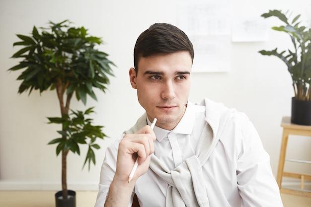 Feche o retrato do jovem designer europeu masculino barbeado bonito tendo olhar pensativo enquanto trabalhava no local de trabalho, pensando em novas idéias e soluções. pessoas, trabalho, talento e criatividade