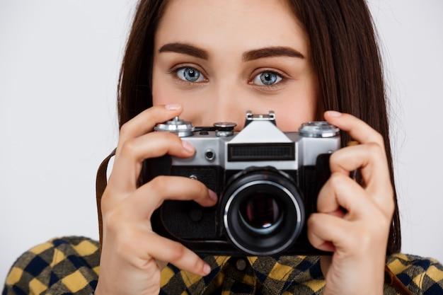 Feche o retrato do jovem fotógrafo moreno bonito sobre parede branca.