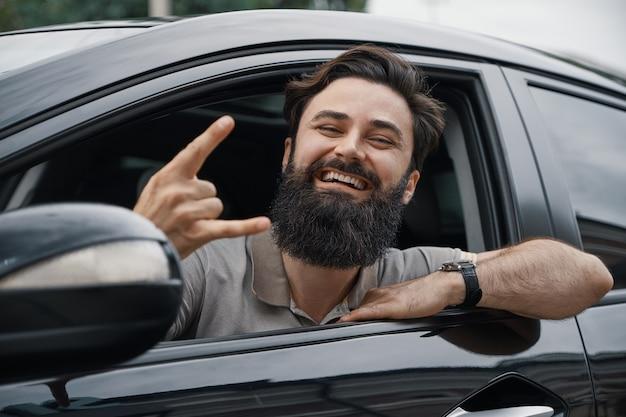 Feche o retrato do lado do homem feliz, dirigindo o carro