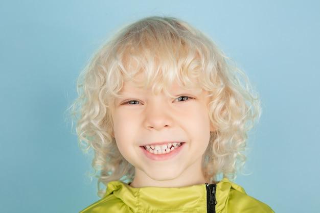 Feche o retrato do lindo garotinho caucasiano isolado na parede azul do estúdio