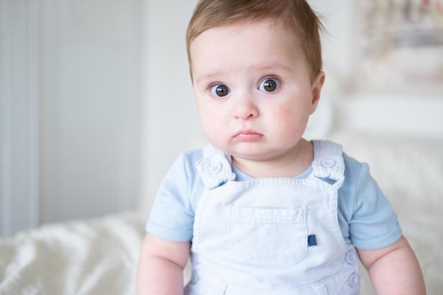 Feche o retrato do menino de 6 meses de idade com roupas blu, sorrindo e sentado na cama branca em casa.