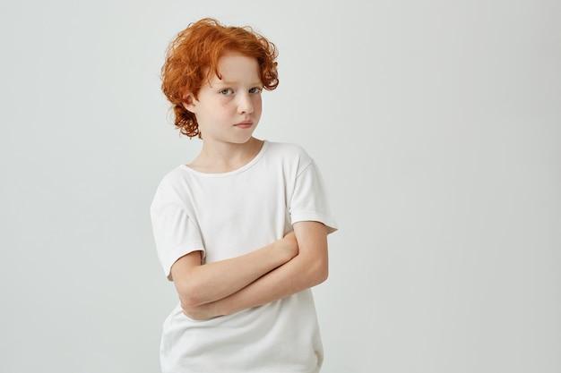 Feche o retrato do menino gengibre engraçado com sardas na camiseta branca, olhando com expressão relaxada e mãos cruzadas.