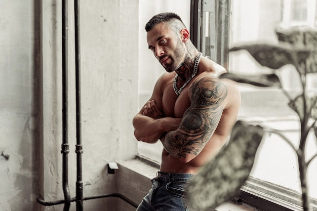 Feche o retrato do modelo masculino nu sexy com tatuagem e olhos mágicos, em pose quente perto perto da janela. interior de quarto loft com muro de concreto cinza.